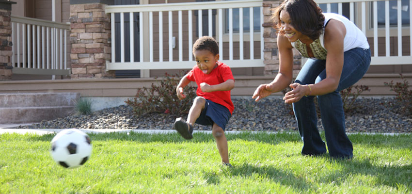 Mom and son playing soccer
